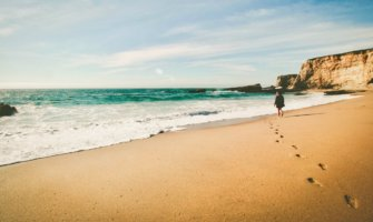 A solo female traveler walking alone on a sandy beach