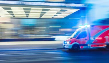 An ambulance driving quickly at night with flashing lights