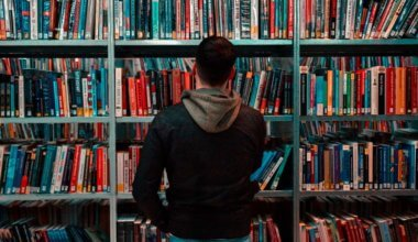 A man looking at a bookshelf in a library