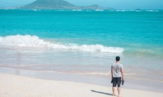 Nomadic Matt alone on a beach in Hawaii