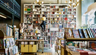 A woman in a bookstore looking at books on a ladder