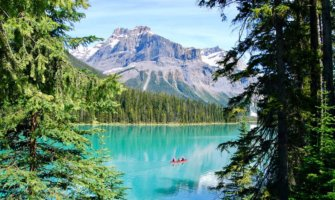 People canoeing on the bright, clear waters of Lake Louise, Alberta, Canada