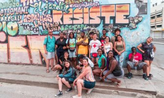 Students from FLYTE on a trip abroad posing near street art