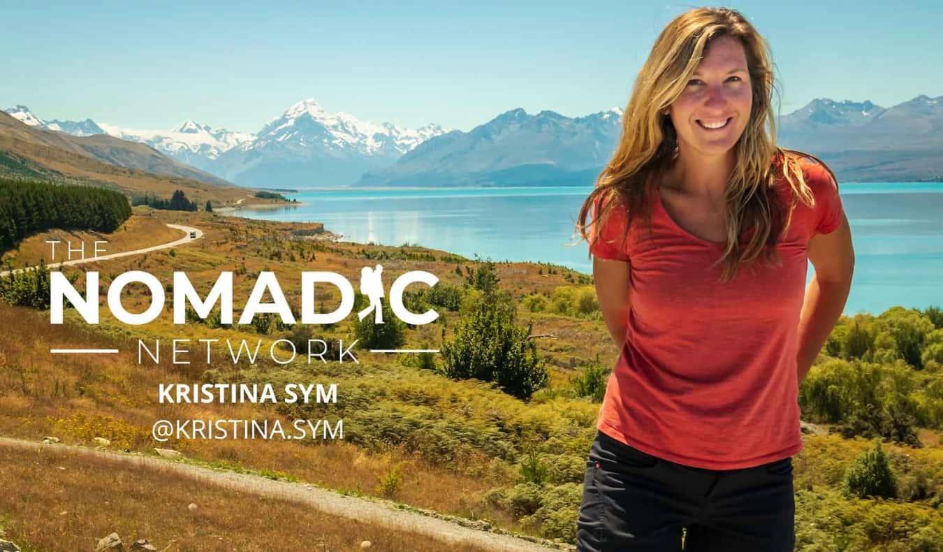 Photographer Kristina Sym posing near a lake and mountains