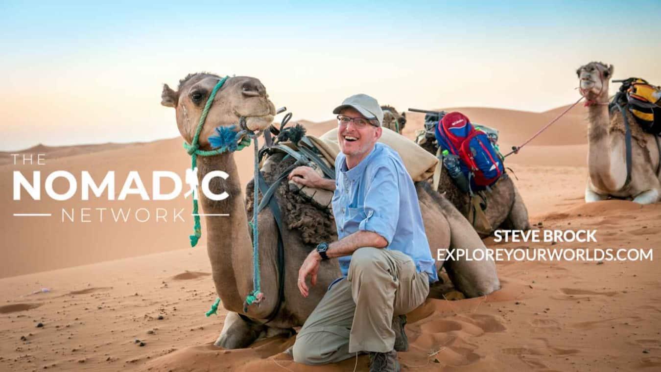 Travel Steve Brock posing beside a camel in the desert