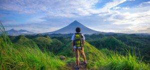 A lone solo traveler posing near a volcano abroad