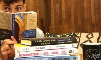 Nomadic Matt reading a pile of books