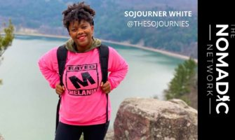 Sojourner White, a woman traveling standing on top of mountain with a lake below her