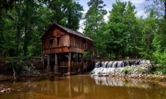 An old wooden building beside a river in the American South