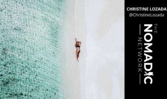 A drone shot of a solo female traveler on a beach overseas