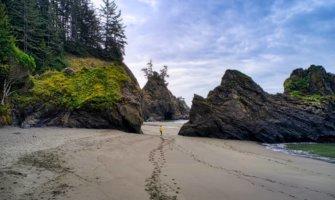 A solo tarveler walking on the beach in Oregon, USA