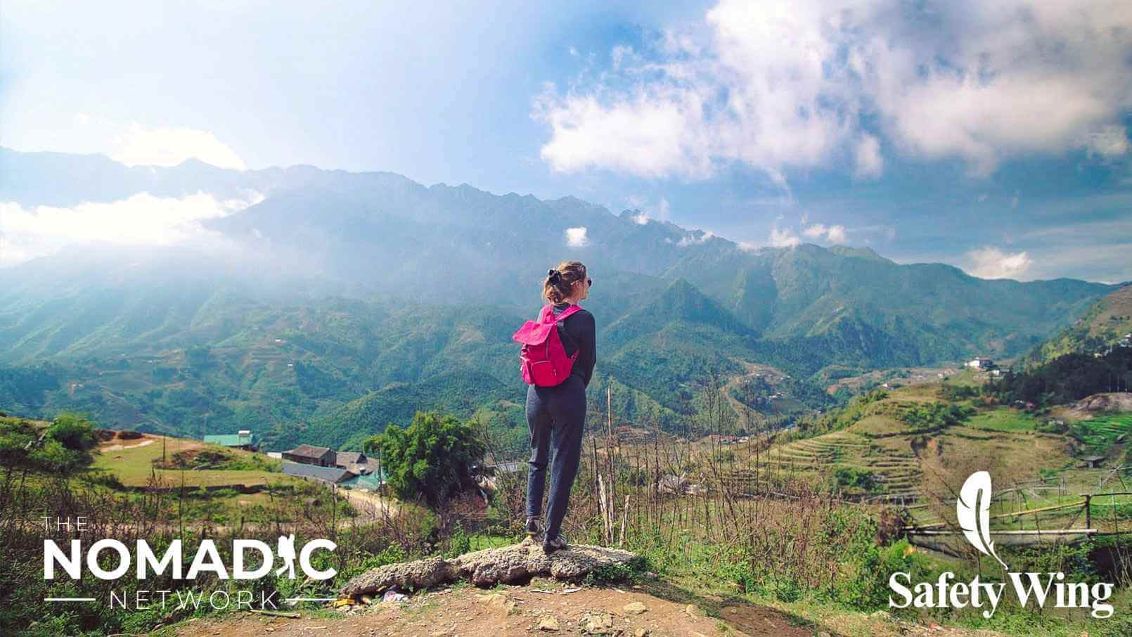 Founder of SafetyWing Sarah Sandnes looks onto lush mountainous landscape while traveling