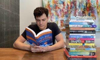 Nomadic Matt reading a pile of books inside at a big desk